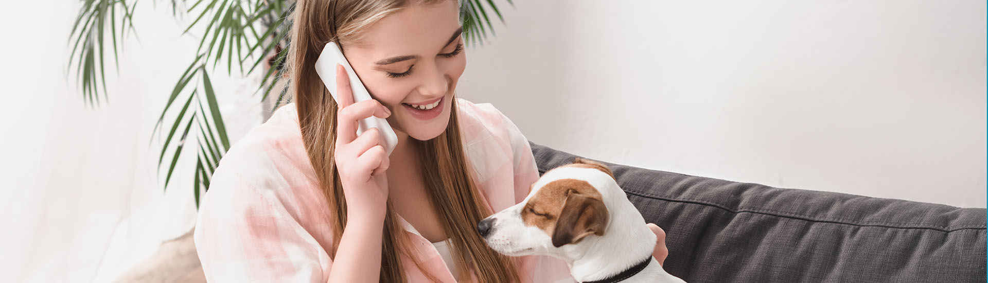 happy woman sitting on couch with jack russell terrier and talking on smartphone